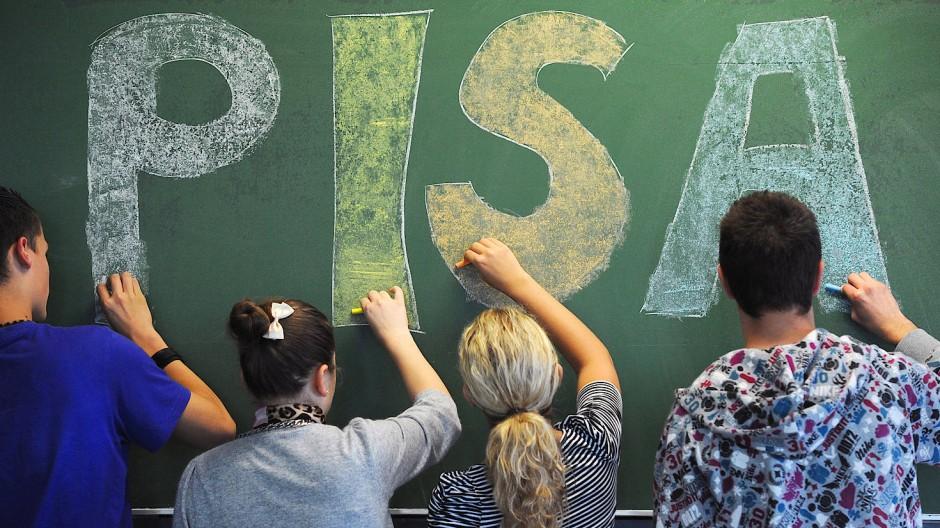 Schüler der neunten Klasse malen in einem Gymnasium in Straubing (Niederbayern) das Wort Pisa auf eine Tafel.