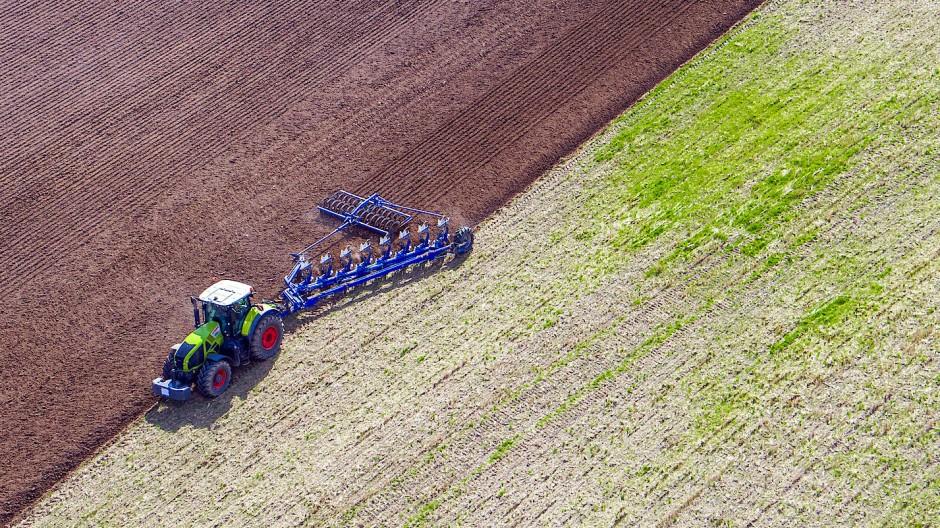 Ein Landwirt in Mecklenburg-Vorpommern pflügt ein abgeerntetes Feld.