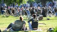 Zahlreiche Menschen sitzen auf Liegestühlen und auf der Wiese in der untergehenden Sonne am Sonntagabend im Berliner James-Simon-Park.