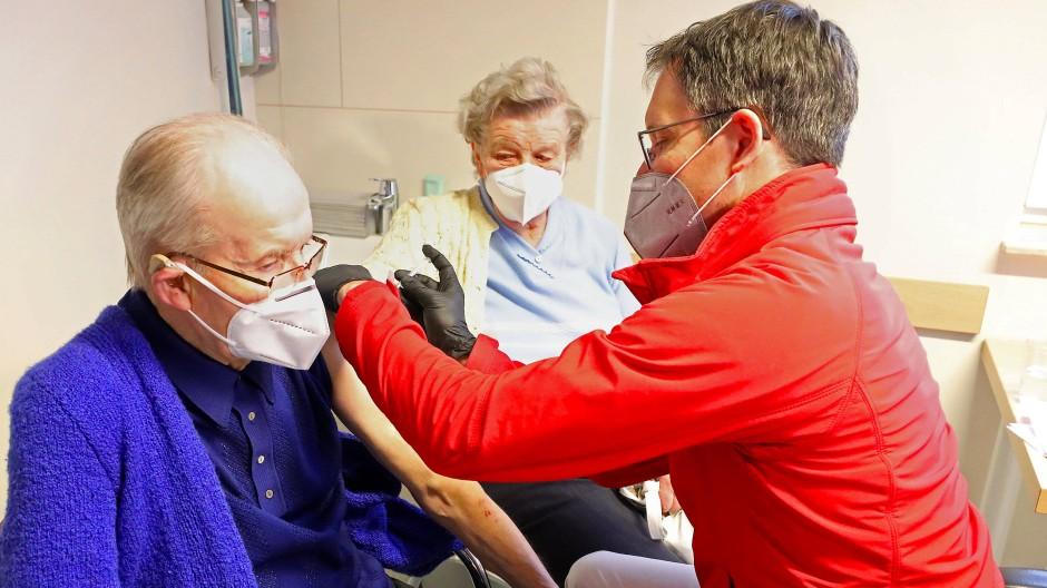 In einer hausärztlichen Gemeinschaftspraxis in Neuburg erhalten zwei Senioren die erste Corona-Schutzimpfung.