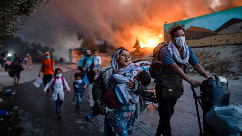 Migranten fliehen am 9. September 2020 vor dem Brand im Flüchtlingslager Moria auf Lesbos
