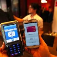 Smartphone mit My-Wallet-App (rechts) neben Empfangsgerät an der Kasse
