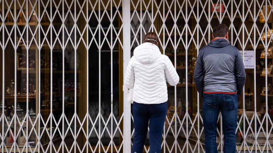 Passanten stehen in der Münchener Fußgängerzone vor einem geschlossenen Geschäft.