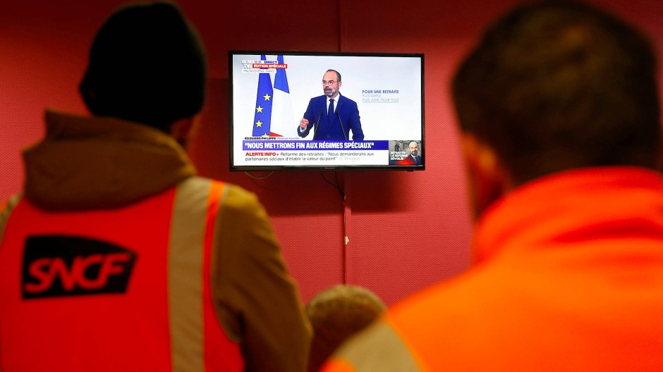 Streikende Eisenbahner verfolgen die Rede, in der Premierminister Edouard Philippe seine Rentenreform vorstellt.