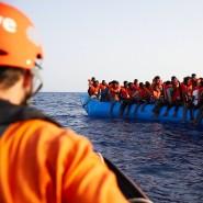 """Seenotrettung ist """"allein nicht die Lösung"""": Ein Seenotretter schaut zu einem Flüchtlingsboot."""