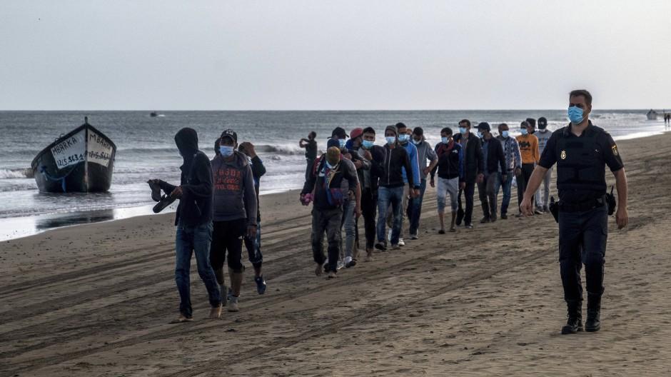 Marokkanische Migranten werden im Oktober 2020 auf den Kanaren von der Polizei begleitet.