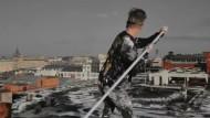 Künstler bemalt ein Fabrikdach in Moskau