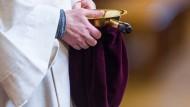 Eine Messdienerin hält im Berliner Dom einen Klingelbeutel.
