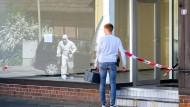 Vor einem Tatort: Ein Polizist und ein Mitarbeiter der Spurensicherung (in der Spiegelung) untersuchen das Haus in Wittingen.