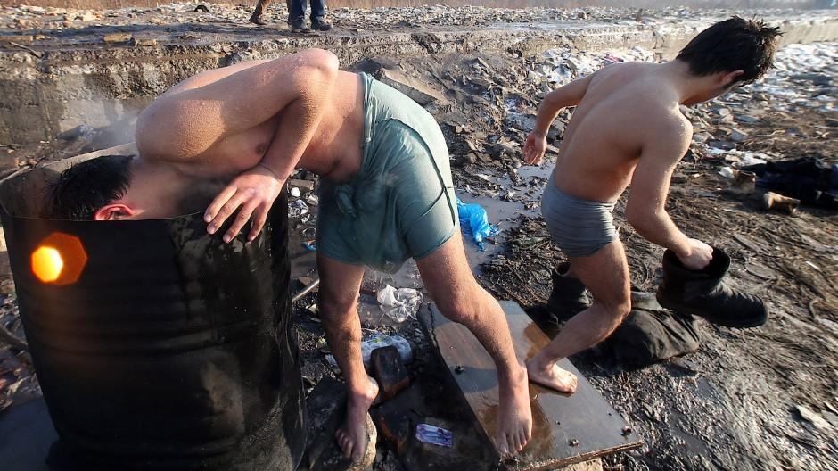 Flüchtlinge in Belgrad waschen sich