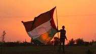 """Vor einem Zeltlager bei Rafah an der Grenze zu Israel hält ein Mann eine palästinensische Fahne. Millionen von Palästinensern kämpfen für ihr """"Recht auf Rückkehr""""."""