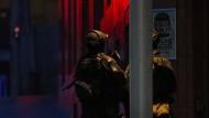 Bewaffnete Polizisten in Sydney nahe des Cafés, in dem seit Stunden etliche Geiseln festgehalten werden.