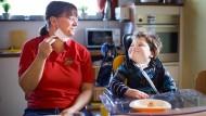 """""""Hauptsache, die Kinder werden angenommen und geliebt."""" Finn zusammen mit einer Mitarbeiterin der """"ARCHE IntensivKinder"""" am Frühstückstisch."""