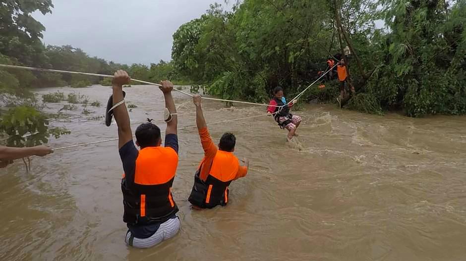 Philippinen, Cagayan: Eine Bewohnerin wird mit Hilfe einer konstruierten Seilbahn evakuiert während Hilfskräfte auf der anderen Seite eines angeschwollenen Flusses warten.