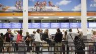 Reisende stehen am Sonntag am Check-In-Schalker von Thomas Cook in London im Flughafen Gatwick.