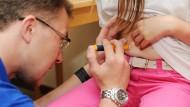 Lästige Pflicht: ein Betreuer spritzt ein an Diabetes erkranktes Mädchen mit einem Insulinpen