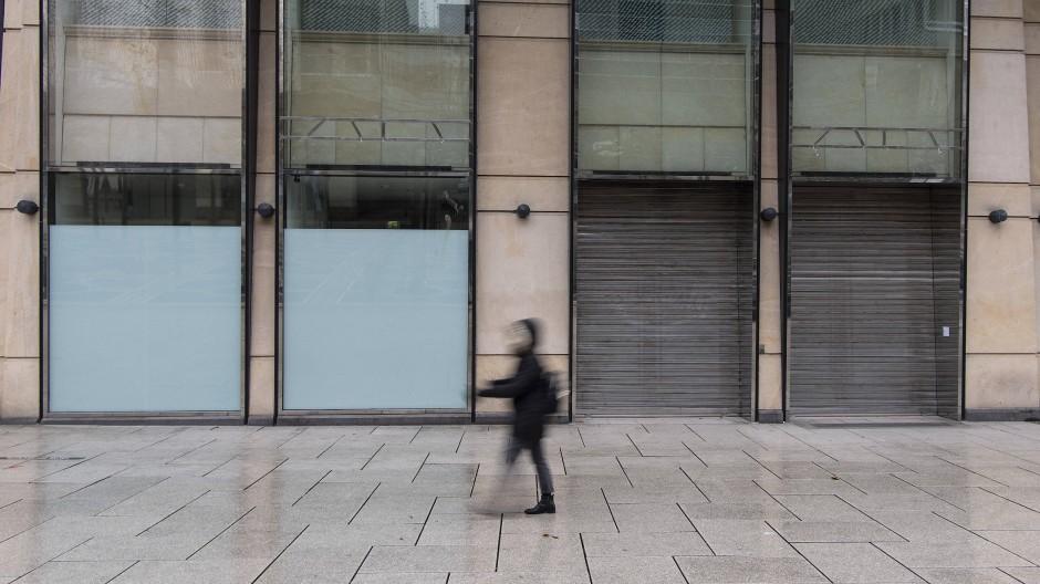 Eine Frau geht auf der Zeil in Frankfurt an geschlossenen Geschäften vorbei.