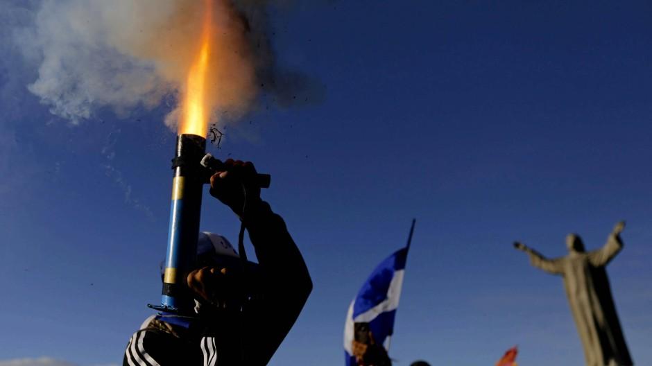 """""""Hier ist nichts normal"""". Ein Demonstrant in Nicaragua feuert einen selbstgebauten Granatenwerfer ab."""