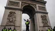 Ein Demonstrant steht am 1. Dezember mit einer Flagge am Triumph-Bogen in Paris