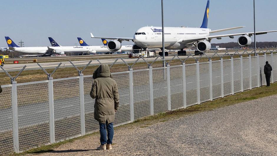Schön Abstand halten: Menschen stehen am Zaun des Frankfurter Flughafens
