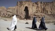 Verschleierte Frauen vor den Sandsteinfelsen in der afghanischen Provinz Bamiyan im Juli 2011. Im Hintergrund sieht man höhlenartige Vertiefungen, in denen einst Buddha-Statuen standen. Bamiyan war im 2. bis 7. Jahrhundert eine buddhistische Klostersiedlung. Im März 2001 zerstörten die zu der Zeit in Afghanistan herrschenden fundamentalistischen Taliban die einzigartigen Bauwerke.
