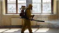 In Moskau desinfizieren Einsatzkräfte wegen Corona einen Bahnhof.