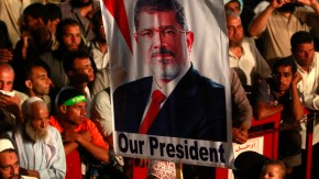 A Mursi supporter holds a banner while taking part in a protest at the Rabaa Adawiya square in Cairo
