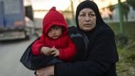 Eine syrische Frau ist mit ihrem Enkel auf der Flucht
