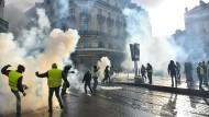 """""""Gelbwesten"""" stehen bei Protesten in Angers am 19. Januar vor einer Wolke aus Tränengas."""