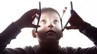 Ein Junge hält sich zwei Smartphones wie Scheuklappen neben die Augen.