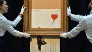 """Mitarbeiter von Sotheby's präsentieren die letzten Fetzen von Banksys """"Girl with Balloon""""."""
