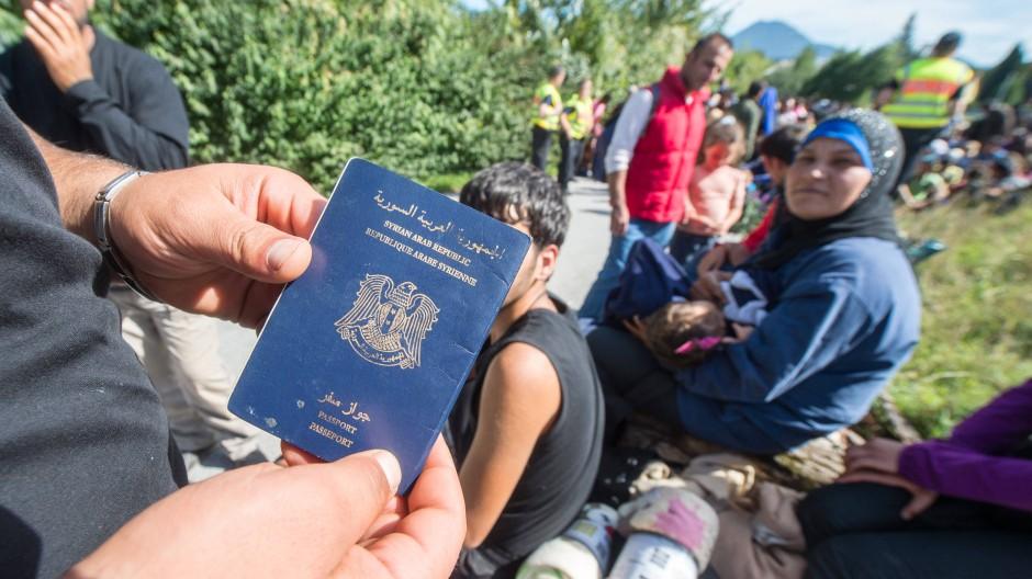 Ein Flüchtling zeigt an der deutsch-österreichischen Grenze seinen syrischen Pass.