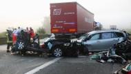 Rettungskräfte vor den völlig zerstörten Fahrzeugen am Unglücksort, der Autobahn 3 bei Nürnberg.
