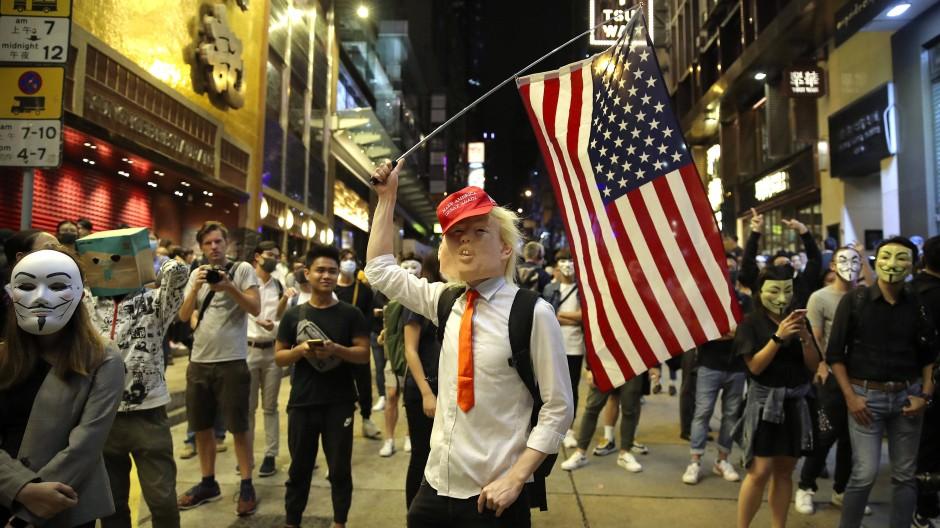 Ein als Donald Trump verkleideter Demonstrant in Hongkong schwenkt während eines Protestes eine amerikanische Fahne.