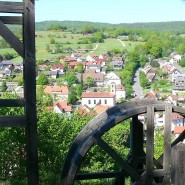 Über ein Tretrad blickt man von Burg Bartenstein auf Partenstein.