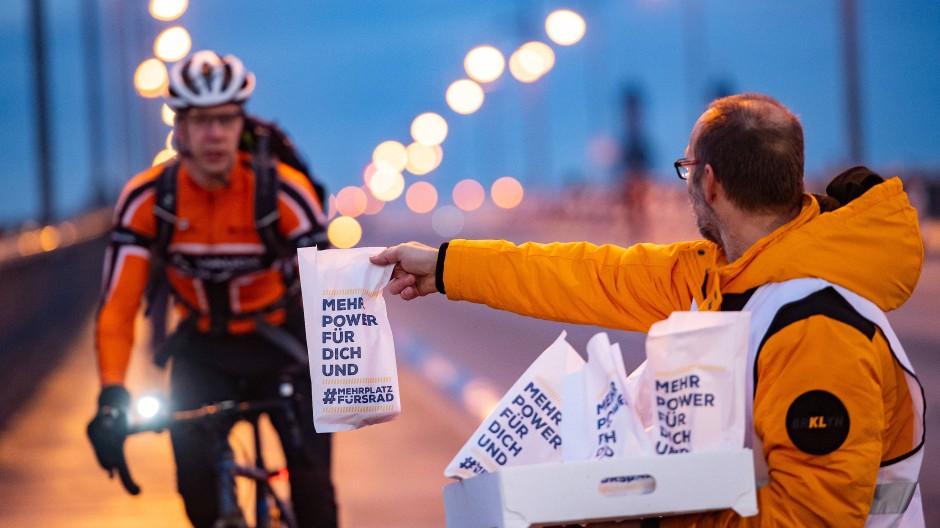Dankeschön: Der Allgemeine Deutsche Fahrrad-Club verteilt im Januar auf der für Autos gesperrten Theodor-Heuss-Brücke Äpfel und Kreppel. Die Stärkung bekommen Pendler, die aufs Velo umgestiegen sind.
