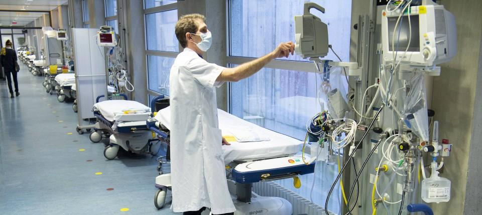 Ein Arzt bereitet in einem Korridor im Krankenhaus von Lausanne Betten für eine mögliche Ankunft neuer Covid-10-Patienten vor.
