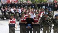Massenverhaftung: Türkische Polizisten und Soldaten eskortieren den ehemaligen türkischen Luftwaffengeneral Akin Ozturk (vorne Mitte) sowie andere Männer zu einem Prozess.