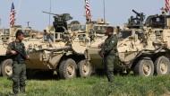 Kurdische Kämpfer stehen nahe der türkisch-syrischen Grenze vor amerikanischen Kampffahrzeugen.