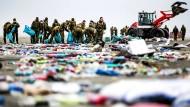 Niederländische Soldaten sammeln an der Küste verstreute Gegenstände