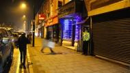 Ein Polizist steht am frühen Donnerstagmorgen vor einem Wohnhaus in Birmingham, das in der Nacht von bewaffneten Polizisten gestürmt wurde. Lebte hier der mutmaßliche Attentäter?