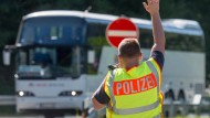 Ein Bundespolizist stoppt einen Bus hinter der deutsch-österreichischen Grenze