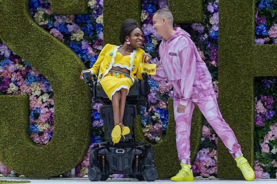 Der Kreativdirektor Jeremy Scott erscheint zum Abschluss seiner Moschino Show mit dem Model Aaron Philip auf dem Laufsteg.