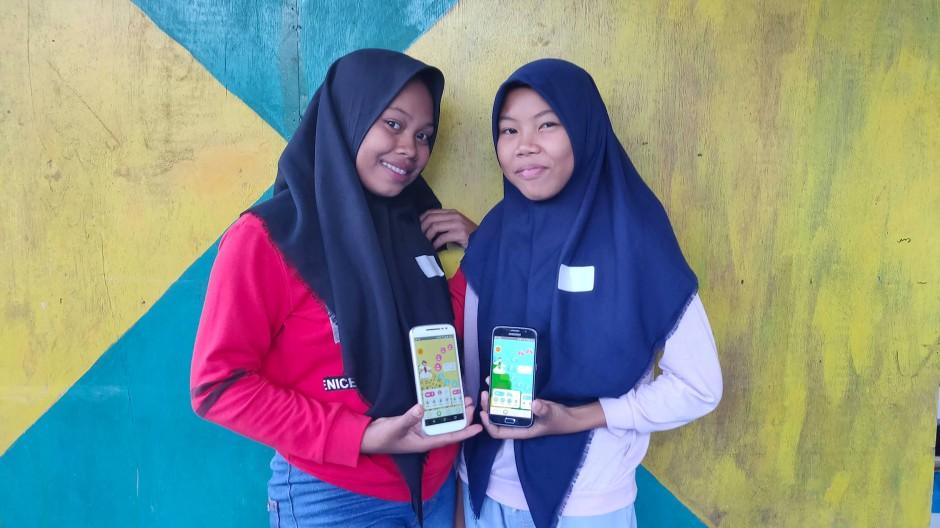 Zwei Mädchen aus Indonesien zeigen die Unicef-App Oky auf ihren Smartphones.