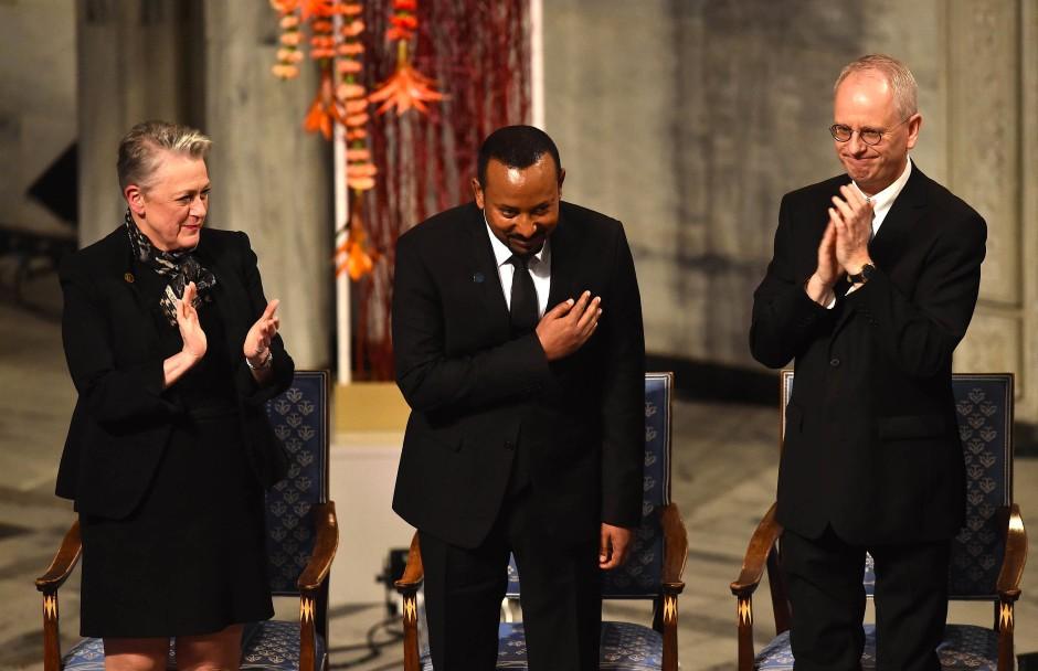 Die Mitglieder des Nobelkomitees, Berit Reiss-Andersen (l) und Henrik Syse (r) applaudieren dem äthiopischen Ministerpräsidenten Abiy Ahmed bei der Nobelpreisverleihung.
