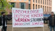 Zwei Demonstranten stehen mit einem Plakat am Auswärtigen Amt. Einige Menschen demonstrierten dort für die Rückführung der Kinder von IS-Kämpfern.