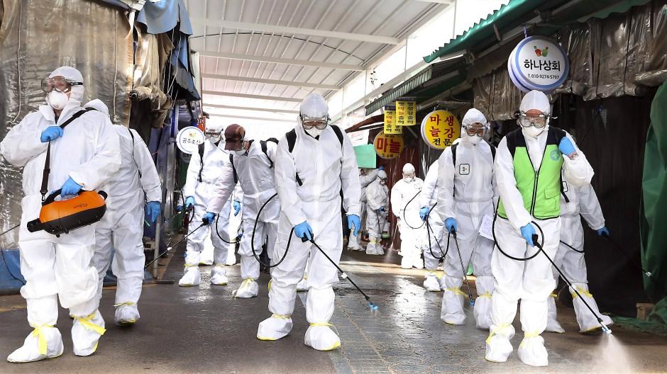 Arbeiterinnen und Arbeiter in Schutzanzügen sprühen Desinfektionsmittel als Vorsichtsmaßnahme gegen die Verbreitung des Coronavirus auf einem Markt in Südkorea.