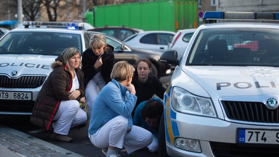 In Deckung: Der Amokschütze eröffnete in einem Wartezimmer des Krankenhauses in Ostrau das Feuer, Mitarbeiter und Patienten flohen auf die Straße.