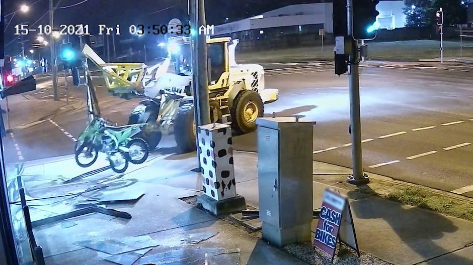 Aufnahmen einer Überwachungskamera zeigen, wie der Dieb am frühen Freitagmorgen zwei Motorräder aus einem Schaufenster stiehlt.