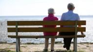 Ausgesorgt: Ein Senioren-Paar sitzt auf einer Bank und schaut auf das Watt.